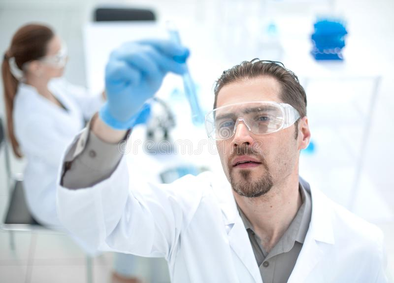 o ο χαμογελώντας επιστήμονας εξετάζει το σωλήνα με το υγρό στοκ εικόνες