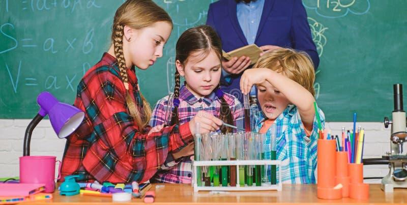 o παιδιά στη χημεία εκμάθησης παλτών εργαστηρίων στο σχολικό εργαστήριο εργαστήριο χημείας παραγωγή του πειράματος στο εργαστήριο στοκ εικόνες
