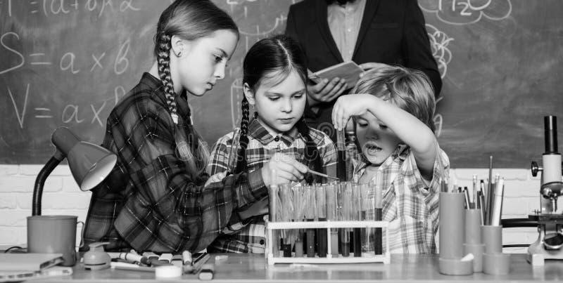 o παιδιά στη χημεία εκμάθησης παλτών εργαστηρίων στο σχολικό εργαστήριο εργαστήριο χημείας παραγωγή του πειράματος στο εργαστήριο στοκ εικόνα με δικαίωμα ελεύθερης χρήσης