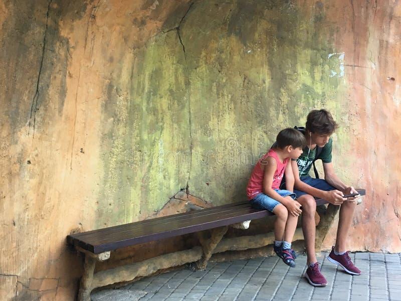 o τα παιδιά χρησιμοποιούν τη συσκευή Προηγούμενος και μελλοντικός Οι έφηβοι χρησιμοποιούν το τηλέφωνο στοκ φωτογραφίες με δικαίωμα ελεύθερης χρήσης