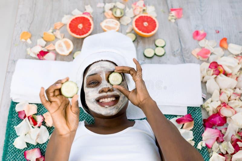 o Τοπ άποψη όμορφο νέο αφρικανικό να εναπόκειται γυναικών στα κομμάτια του αγγουριού στο πρόσωπό της στη SPA στοκ φωτογραφία με δικαίωμα ελεύθερης χρήσης