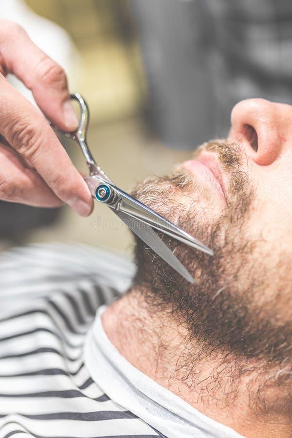 o Взгляд со стороны молодого бородатого человека получая стрижку бороды парикмахером пока сидящ в стуле на парикмахерскае стоковые фотографии rf