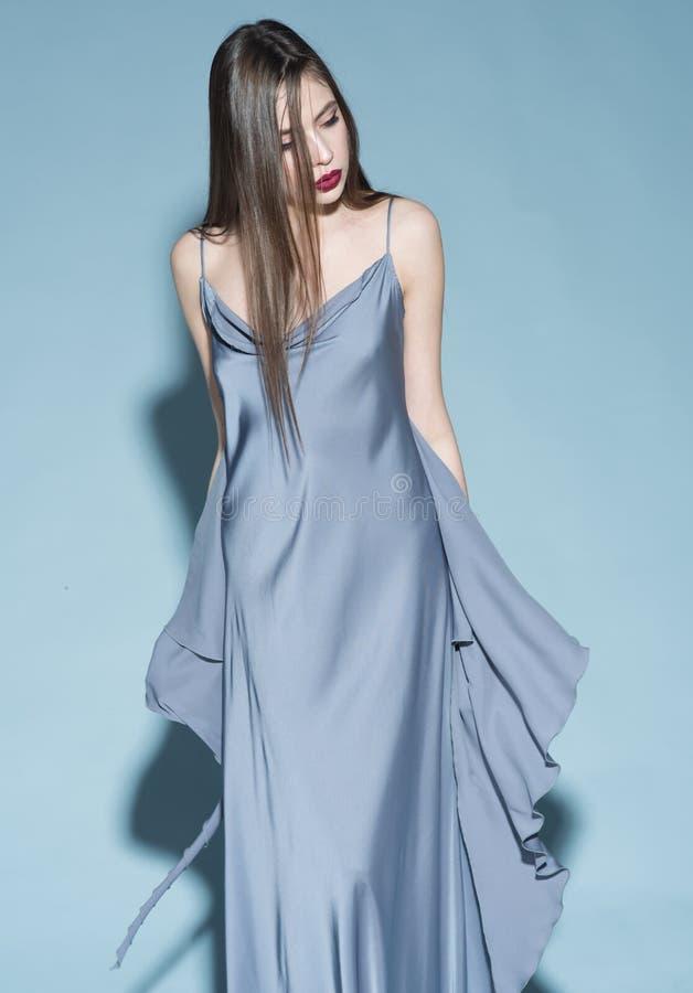 o Девушка на строгой уверенной стороне в длинном голубом платье, светлом - голубая предпосылка Дама с красными губами носит стоковая фотография rf