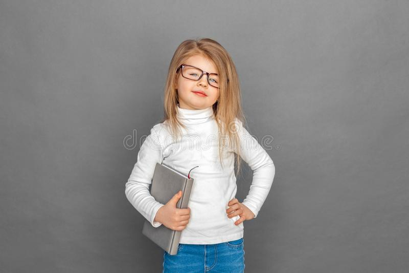 o Маленькая девочка в eyeglasses стоя изолированная на сером цвете с организатором представляя усмехаться уверенный стоковые фотографии rf