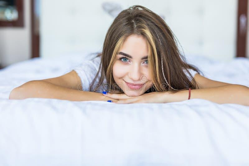 o Молодая женщина смотря камеру и усмехаясь пока лежащ на кровати дома стоковое фото rf