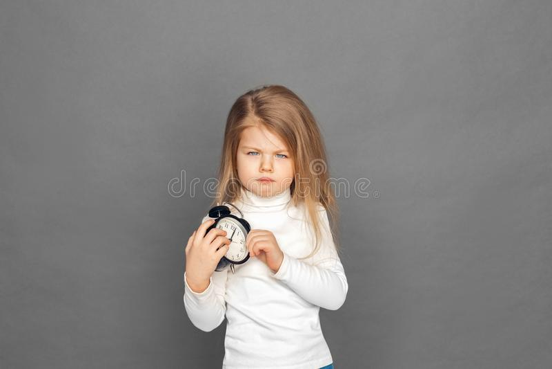 o Положение маленькой девочки изолированное на сером цвете с гримасничать будильника несчастный к камере стоковые изображения rf