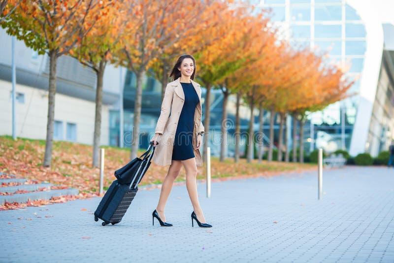 o Усмехаясь женское продолжение пассажира к воротам выхода вытягивая чемодан через конкурс аэропорта стоковая фотография rf