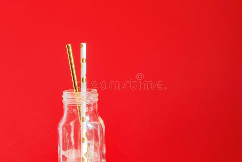 o 在玻璃葡萄酒瓶的纸recycable饮用的鸡尾酒会秸杆在红色背景 库存图片