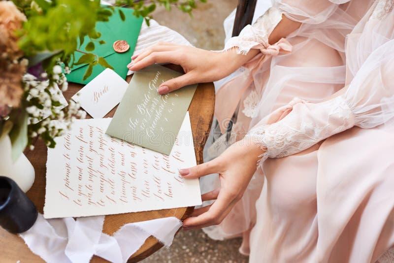 o 新娘在窗口附近坐并且读信给新郎 婚礼誓约 ?? r 图库摄影