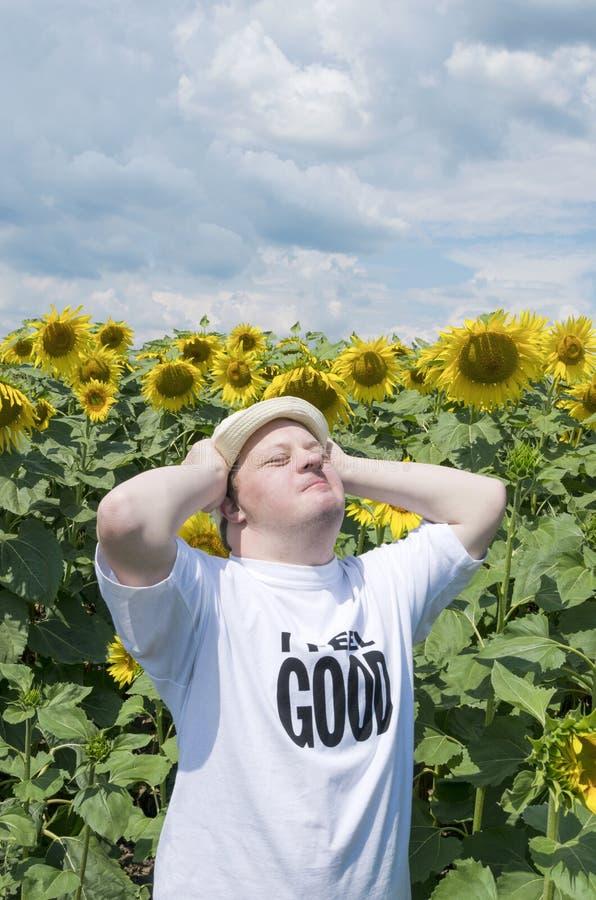 o 有感到好和放松在开花的领域的唐氏综合症的人 库存照片