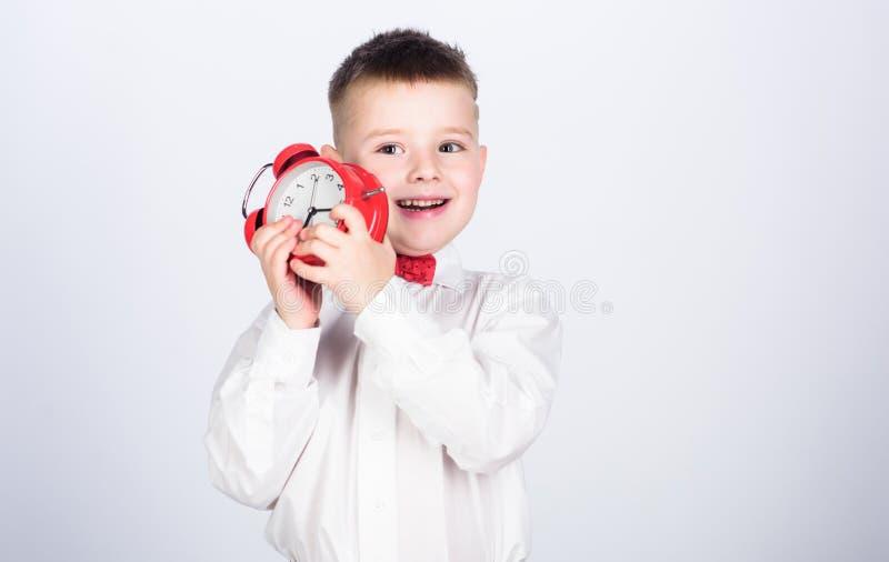 o ?? 有闹钟的小男孩 时刻放松 E ?? ?? 无尾礼服孩子 免版税库存图片