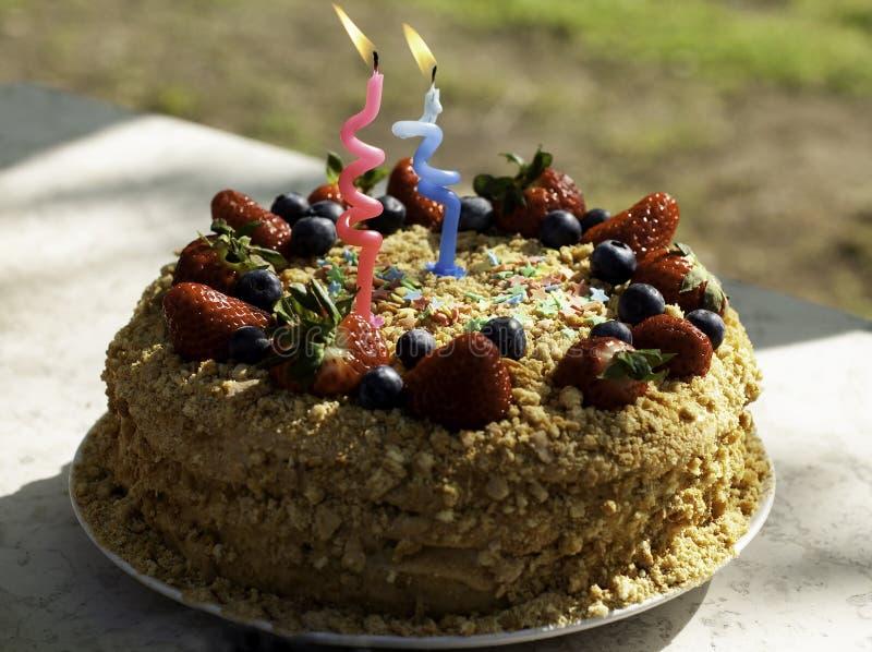 o 用蜡烛为生日装饰的自创蛋糕,蓝莓,草莓 免版税库存照片