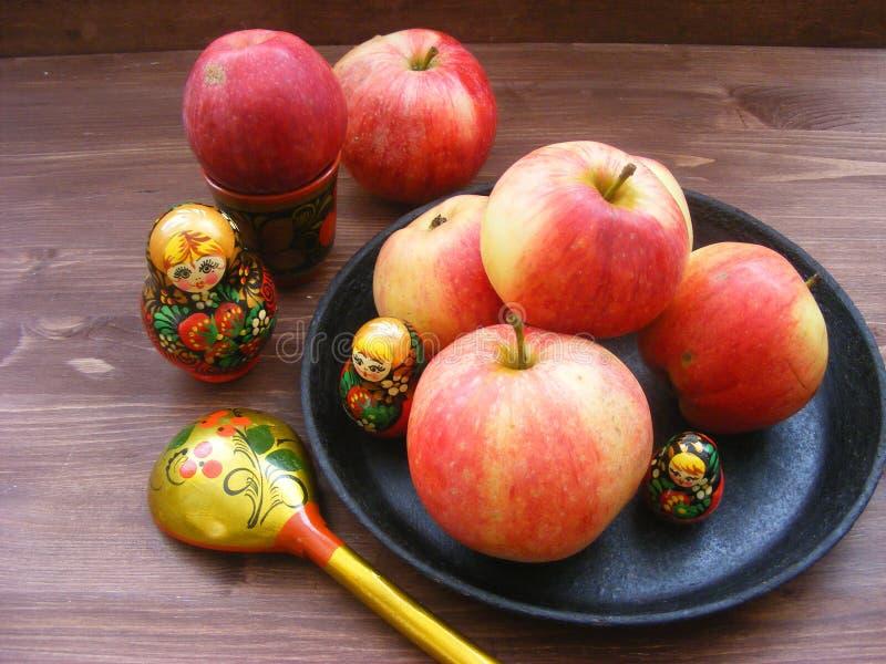 o 红色和黄色苹果的构成在黑生铁板材的有传统俄国筑巢玩偶matrioshka的 库存图片