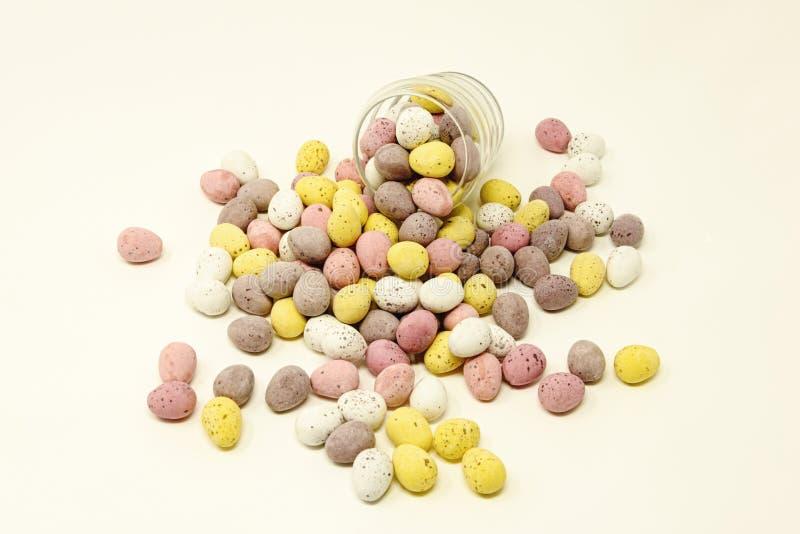 O açúcar brilhantemente colorido pequeno revestiu os ovos da páscoa do chocolate que derramam para fora de e que apoiam um copo d fotos de stock royalty free
