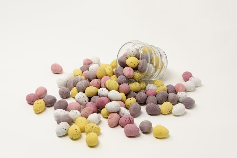 O açúcar brilhantemente colorido pequeno revestiu os ovos da páscoa do chocolate que derramam para fora de e que apoiam um copo d foto de stock royalty free