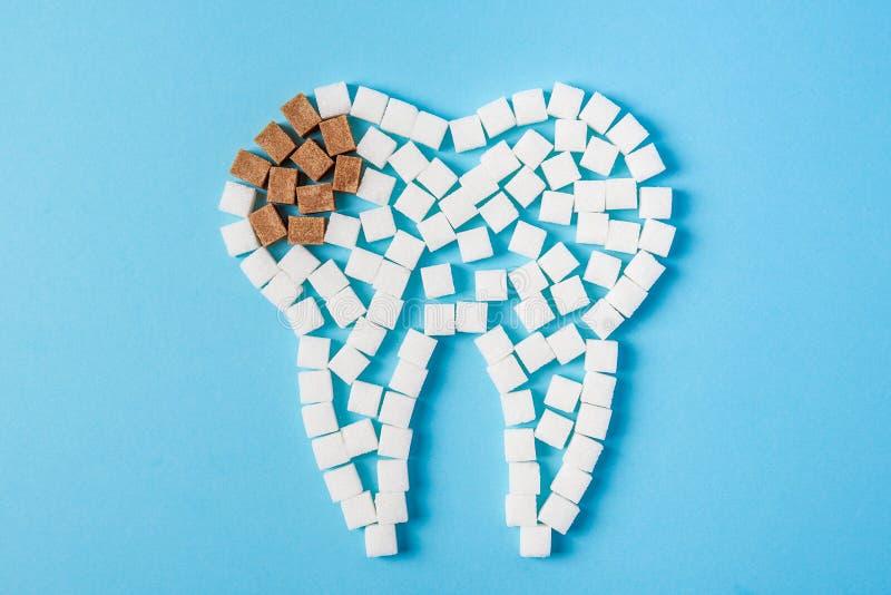 O açúcar destrói o esmalte de dente e condu-lo à deterioração de dente Dente feito do branco e da cárie feitos de cubos do açúcar foto de stock