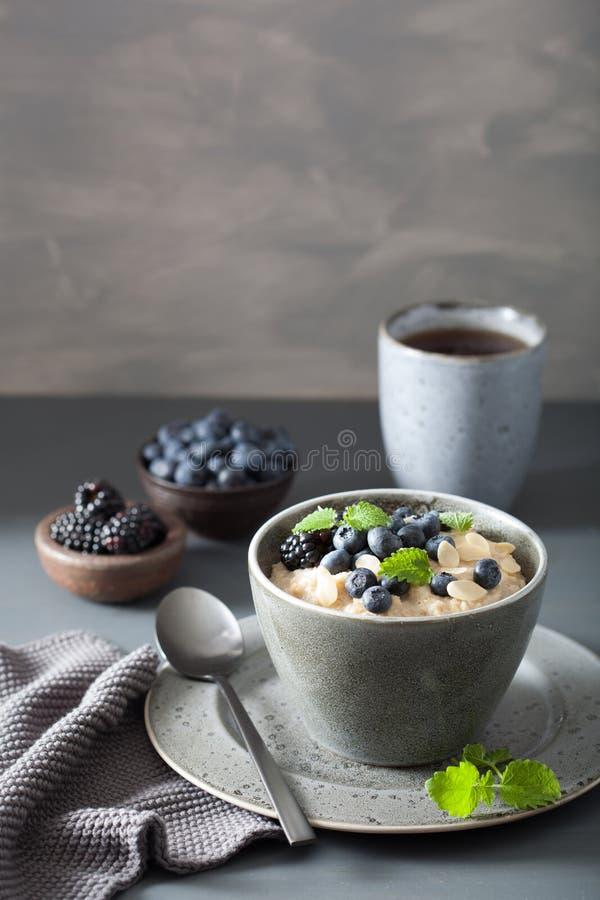 O aço saudável do café da manhã cortou o papa de aveia da farinha de aveia com blac do mirtilo fotografia de stock