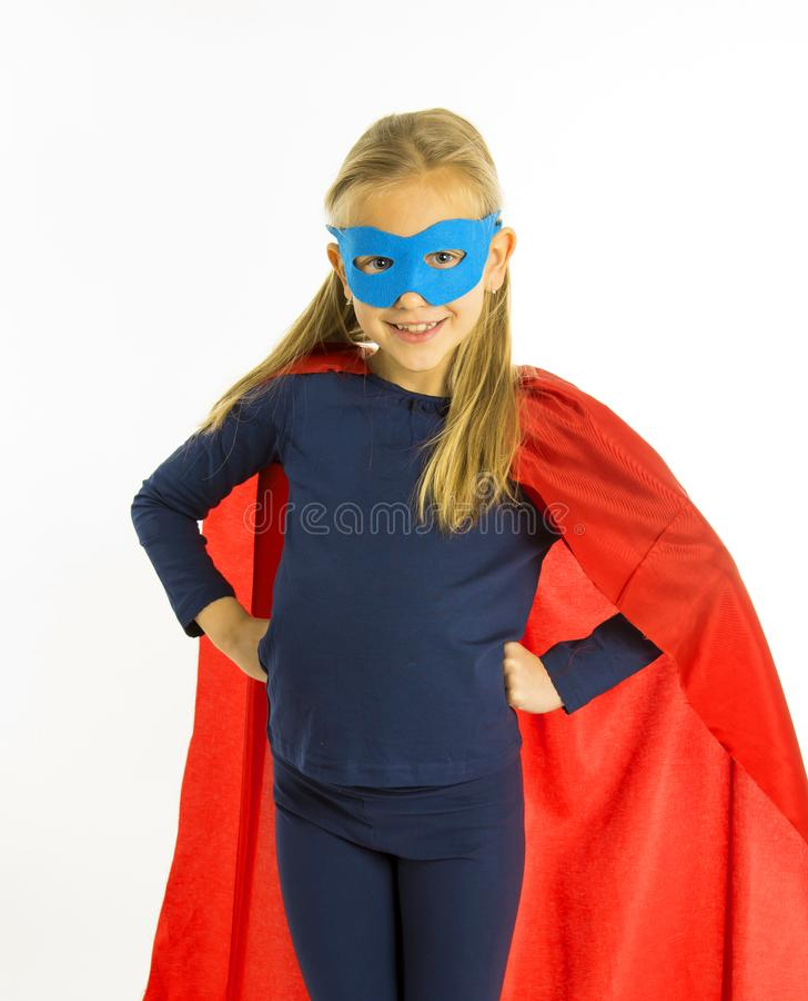 7 o 8 años del niño femenino rubio joven en el traje del superhéroe sobre la ejecución del uniforme escolar feliz y emocionado ai fotografía de archivo