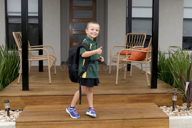6 o 7 años del niño que lleva que lleva femenino de la mochila pesada grande de la escuela de la chica joven del unifor alegre so foto de archivo libre de regalías