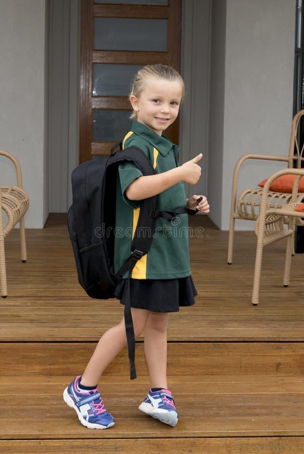 6 o 7 años del niño que lleva que lleva femenino de la mochila pesada grande de la escuela de la chica joven del unifor alegre so imagen de archivo libre de regalías