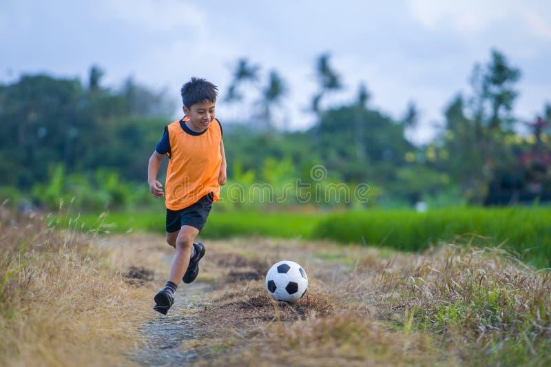 8 o 9 años felices y niño emocionado que juega a fútbol al aire libre en el chaleco del entrenamiento del jardín que lleva que co fotos de archivo