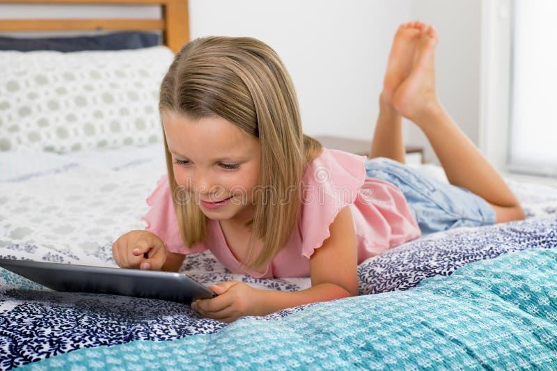 6 o 7 años rubios hermosos de la chica joven que miente en la sonrisa de la cama feliz usando Internet en la observación y el hav foto de archivo libre de regalías
