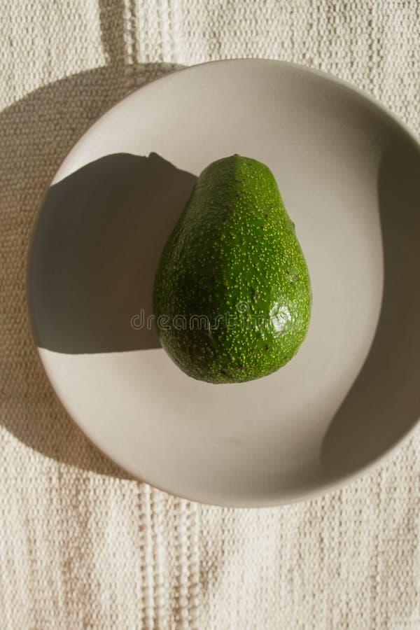 O abacate maduro inteiro verde encontra-se em uma placa cerâmica cinzenta no sol Um abacate está em um tapete natural bege em uma imagens de stock