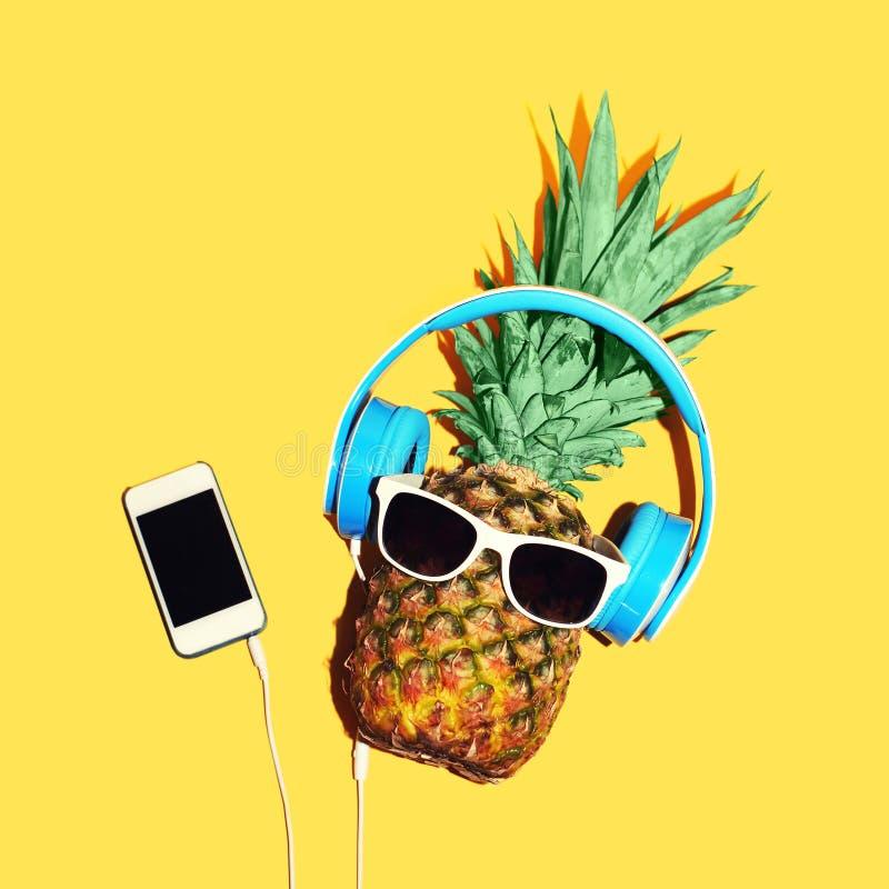 O abacaxi da forma com óculos de sol e fones de ouvido escuta música no smartphone sobre o fundo amarelo imagem de stock royalty free