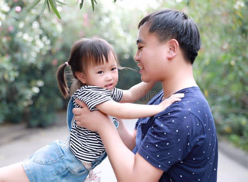 O abraço do abraço do pai seu sorriso da filha manda o divertimento apreciar o tempo livre no jogo feliz da infância da criança d imagem de stock