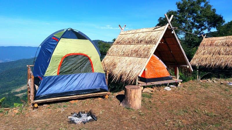 O acampamento azul/verde e barraca da laranja na maca de madeira com o telhado seco das folhas e céu azul, montanha e árvore imagem de stock