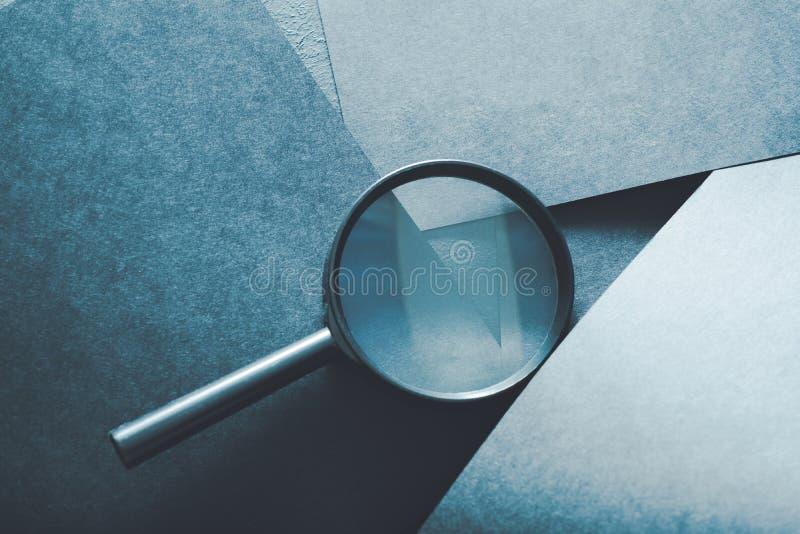 O achado da lupa detecta o fundo do azul da lupa fotografia de stock