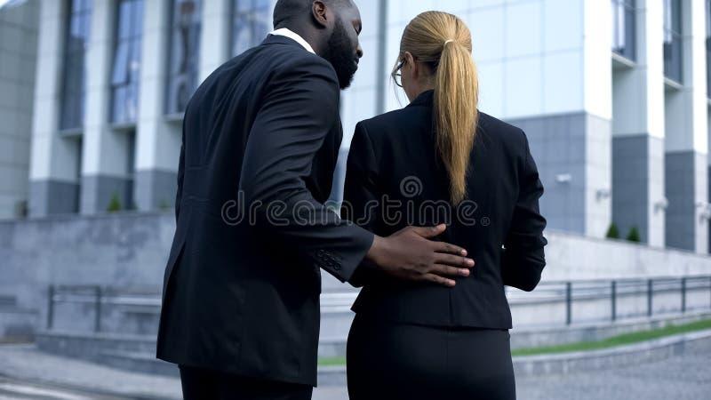 O acosso sexual da mulher de negócio no local de trabalho, chefe comporta-se insultingly foto de stock