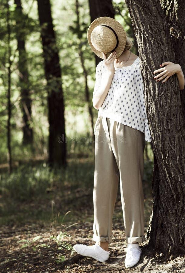 O adolescente à moda da menina cobre sua cara com um chapéu de palha foto de stock