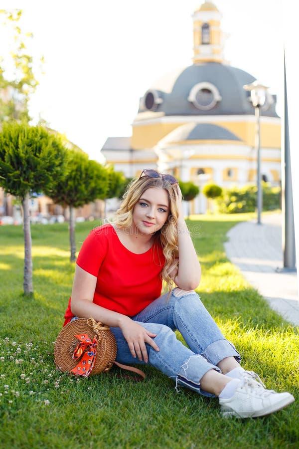 O adolescente à moda weared nas calças de brim e no t-shirt vermelho que sentam-se na grama imagem de stock royalty free
