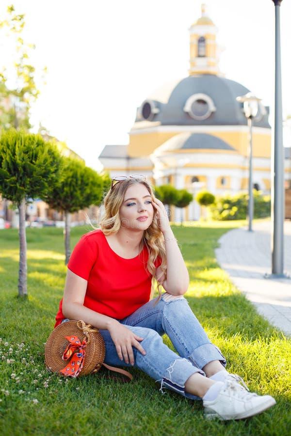 O adolescente à moda weared nas calças de brim e no t-shirt vermelho que sentam-se na grama fotos de stock royalty free