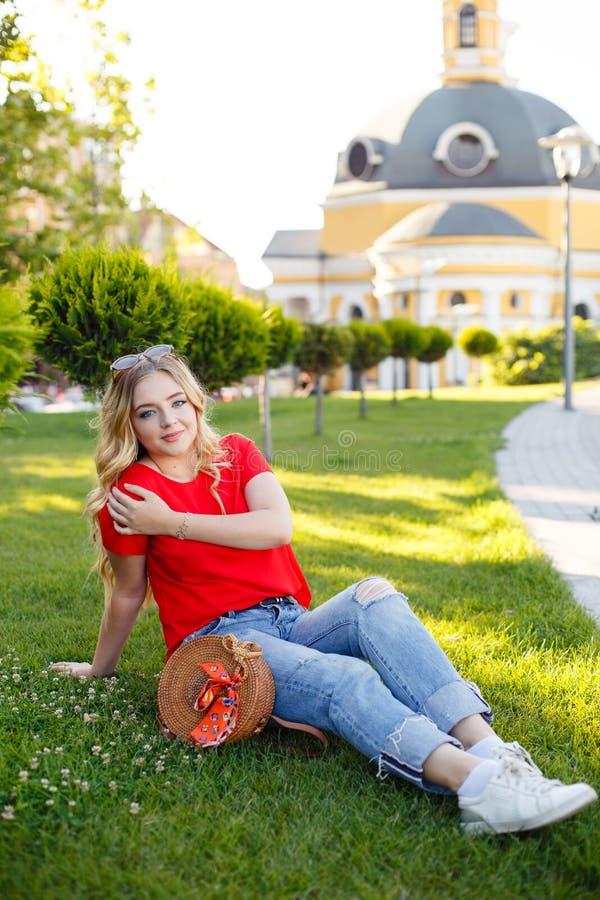 O adolescente à moda weared nas calças de brim e no t-shirt vermelho que sentam-se na grama imagens de stock
