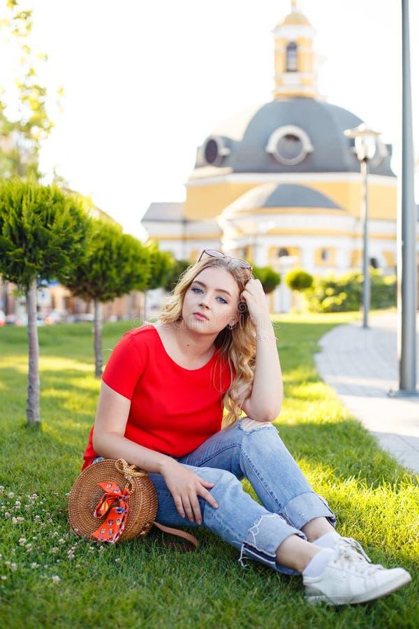 O adolescente à moda weared nas calças de brim e no t-shirt vermelho que sentam-se na grama fotografia de stock royalty free