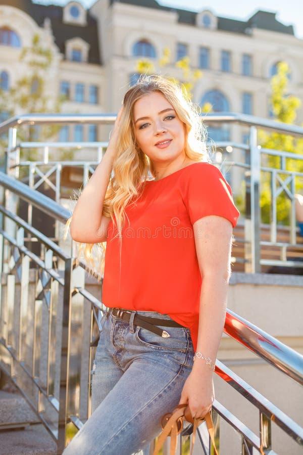 O adolescente à moda weared nas calças de brim e no t-shirt vermelho que sentam-se na grama imagens de stock royalty free