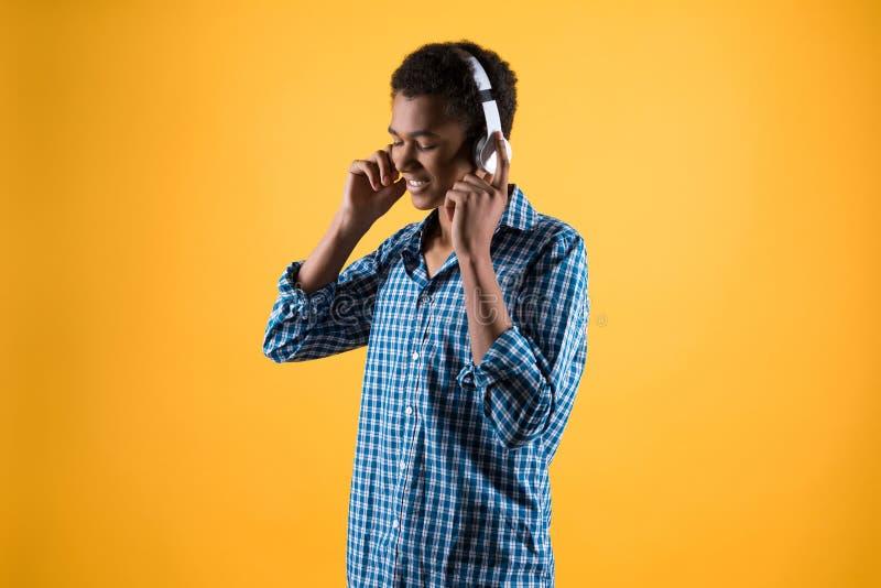 O adolescente afro-americano nos fones de ouvido escuta a música foto de stock royalty free