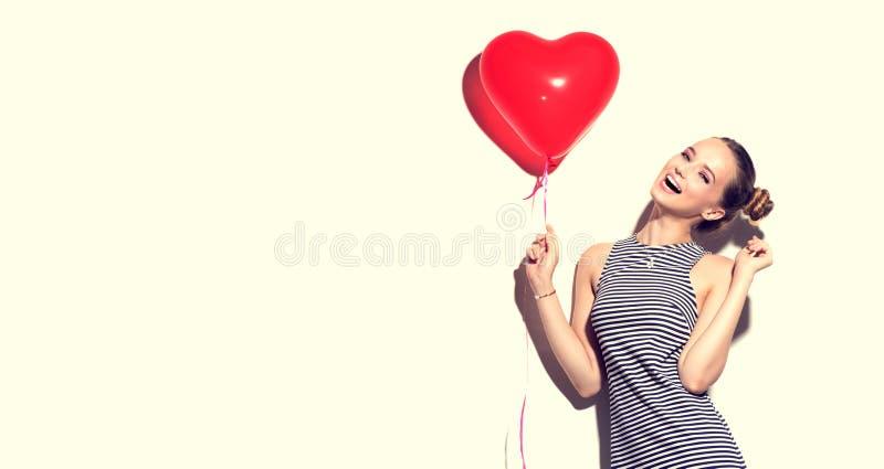 O adolescente alegre da beleza com coração deu forma ao balão de ar imagens de stock royalty free