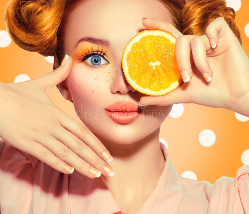 O adolescente alegre da beleza toma laranjas suculentas Menina modelo adolescente com sardas, penteado vermelho engraçado, compos fotografia de stock