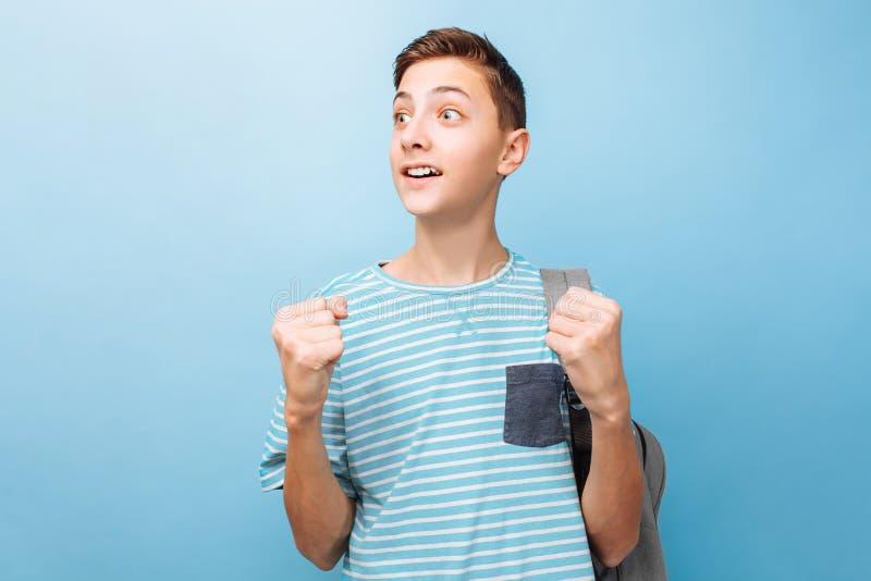 O adolescente alegre, o indivíduo comemora seu sucesso, aperta seus punhos, mostra um gesto da vitória imagem de stock royalty free