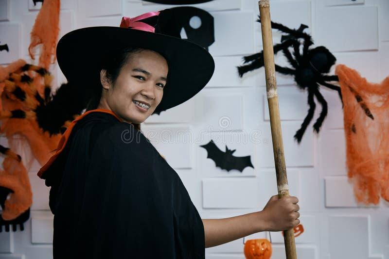 O adolescente alegre na bruxa traja a comemoração do levantamento de Dia das Bruxas imagens de stock royalty free