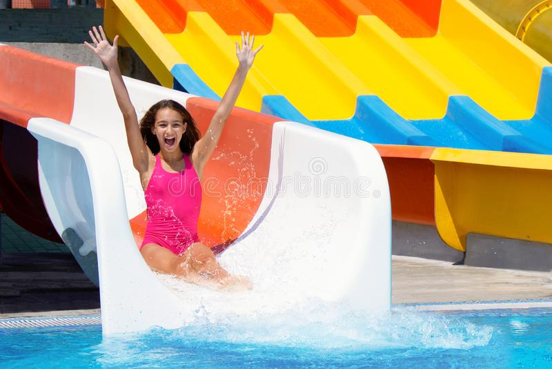 O adolescente alegre que vai para baixo na corrediça de água faz a água que espirra no parque do aqua fotos de stock