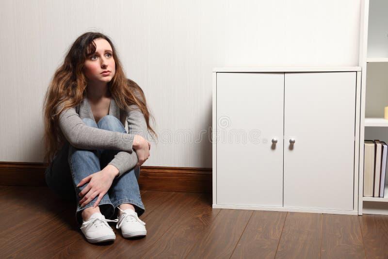 O adolescente ansioso senta-se sozinho no assoalho em casa foto de stock royalty free