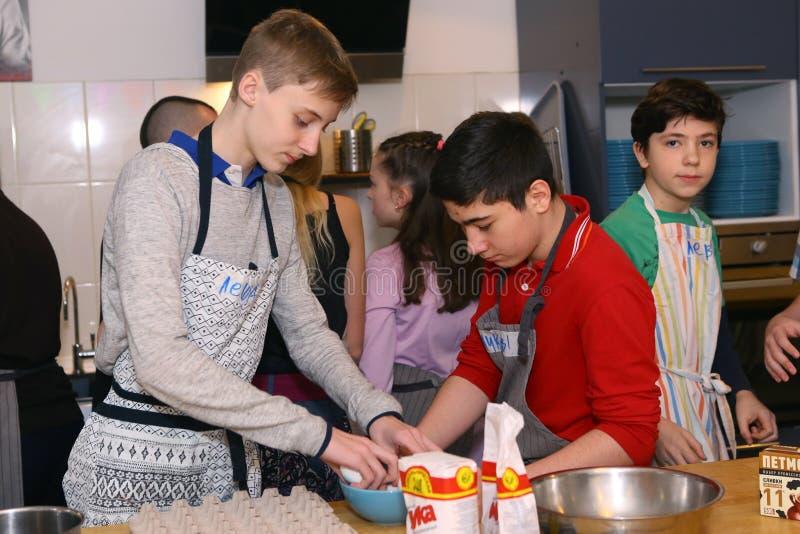 O adolescente caçoa a equipe que cozinha tendo o divertimento imagens de stock