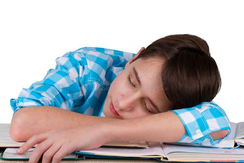 O adolescente cansado dorme sobre os livros após ter feito uns trabalhos de casa imagens de stock