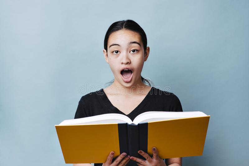 O adolescente chocou a expressão ao ler um conceito da educação do livro de texto foto de stock royalty free