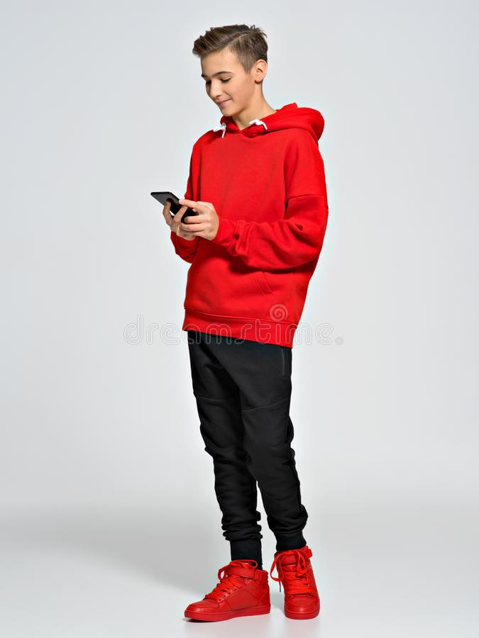 O adolescente considerável guarda o telefone celular nas mãos imagem de stock royalty free