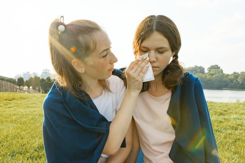 O adolescente consola-a que grita, amigo virado, triste As meninas estão sentando-se na grama verde no parque imagens de stock royalty free